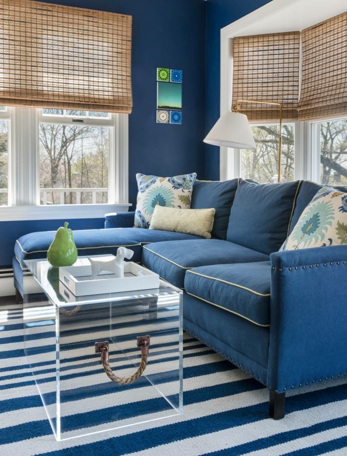 Sofa maritim in blauer Farbe, dunkelblau gefärbte Wand, durchsichtiger Tisch in Form von einer Truhe, blau weißer Teppich