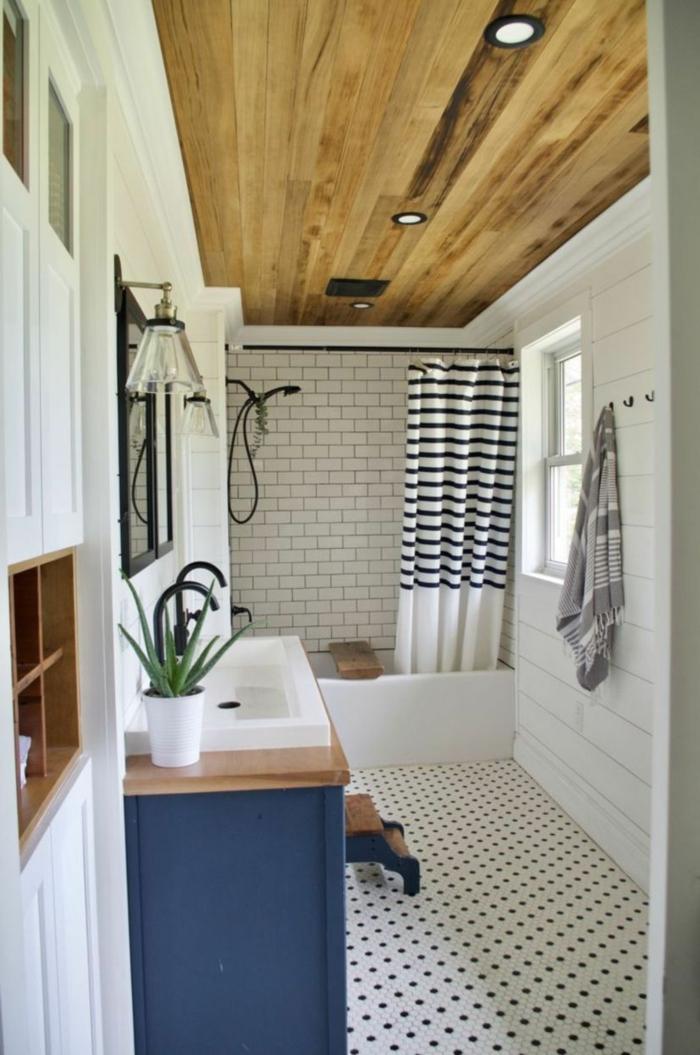 kleines Badezimmer maritime Einrichtung, Badewanne mit blau weißem Duschvorhang, blaue Kommode mit weißem Waschbecken
