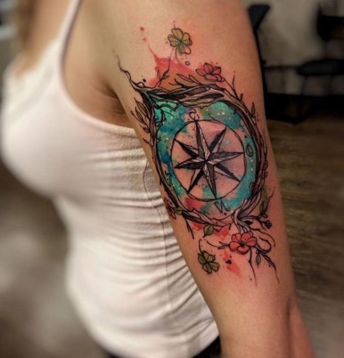das ist eine idee für einen compass tattoo für frauen - ein kompass und kleine grüne und rote blumen