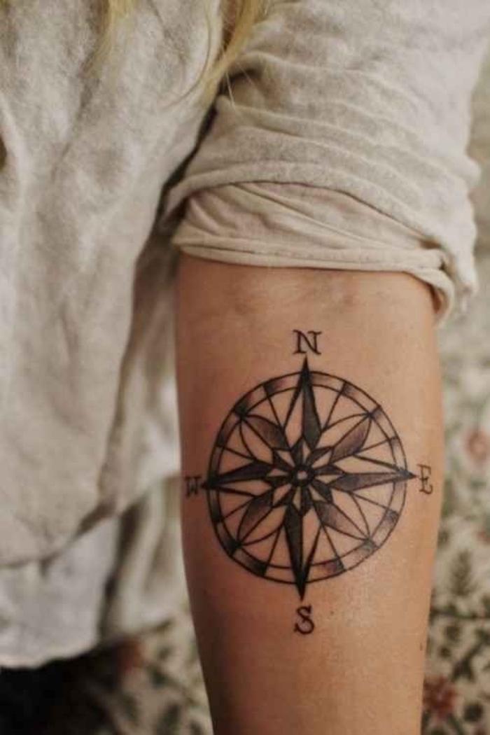 eine hand mit einem schwarzen tattoo mit einem schwarzen kompass