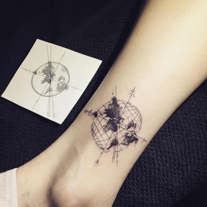 hier zeigen wir ihnen noch eine idee für einen tattoo auf bein mit einem schwarzen kompass mit erde, planeten und schwarzen pfeilen