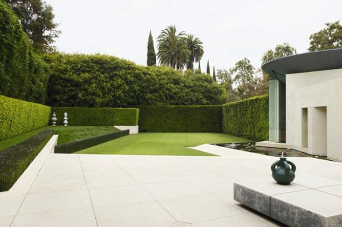 ein bildschönes minimalistisches Design von Vorgarten mit hohen Hecke