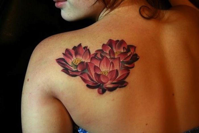 farbiges Tattoo, drei rote Blumen, sich eine Tätowierung am Rücken/an der Schulter stechen lassen
