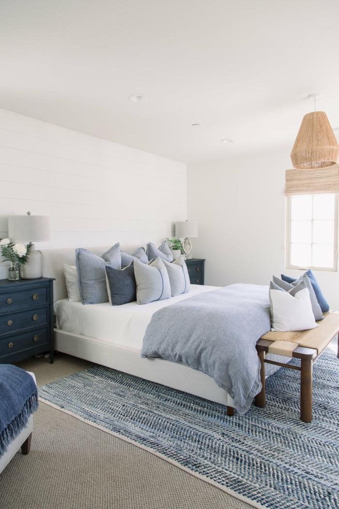 kleine blaue Kommode, Schlafzimmereinrichtung im maritimen Stil, maritime Farben, blaue Bettwäsche und Teppich