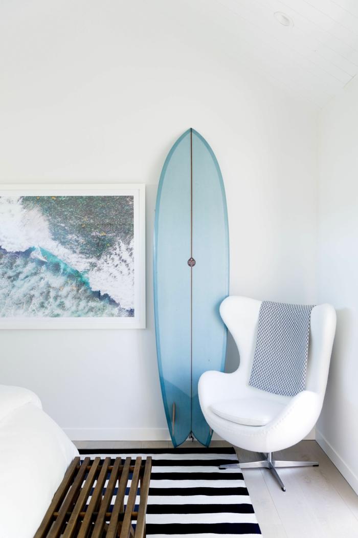 Teppich maritim, Schlafzimmer Einrichtung mit nautischen Motiven, blaues Surfbrett als Dekoration, moderner weißer Sessel,