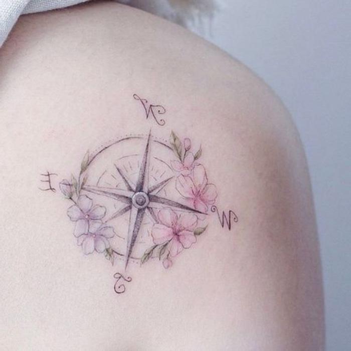 eine sehr schöne tätowierung mit kleinen pinken und lila blumen und einem kompass auf dem
