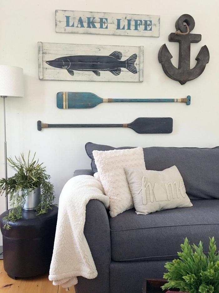 Maritime Möbel. großes blaues Couch, nautische Dekoration an die Wand, zwei aufgehängte Ruder und ein Anker, grüne Pflanzen