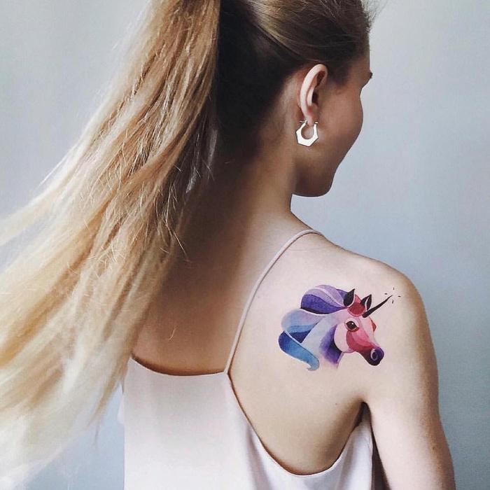 ein Einhorn Tattoo an dem Schulter in lila, roter und blauer Farbe Watercolor Tattoo