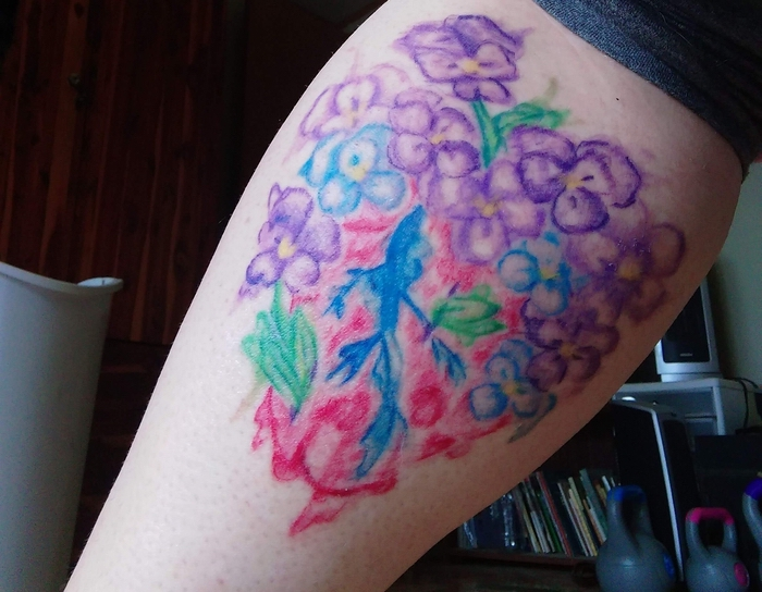 lila und blaue Blumen auf Rotem Hintergrund auf dem Bein Watercolour Tattoo