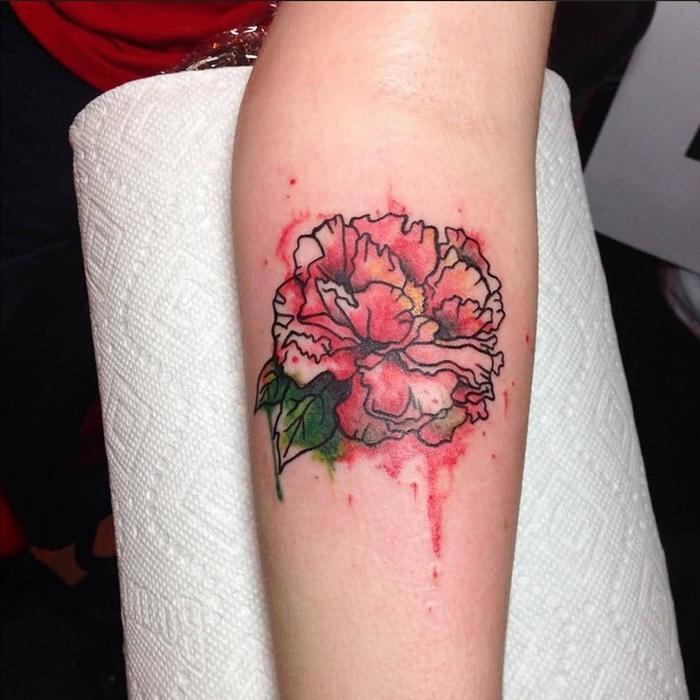 Watercolor Tattoo eine rote Blume und ihre grüne Blätter an dem Arm ganz kunstvoll