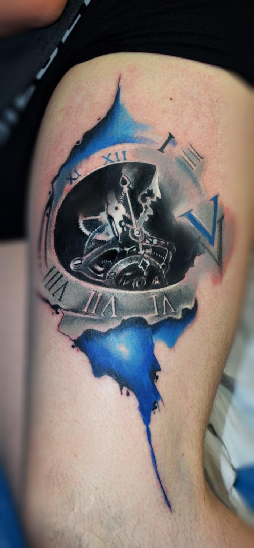 ein silbernes Tattoo mit Steam Punk Motive auf blauem Hintergrund mit Römer Ziffern
