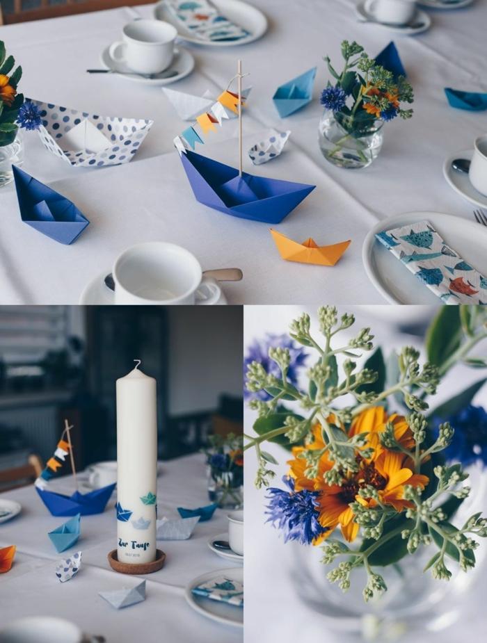 Maritime Tischdeko für Taufe, große weiße Kerze bestempelt mit Segelboote, Blumen in orange und blau, Servietten mit Fischen