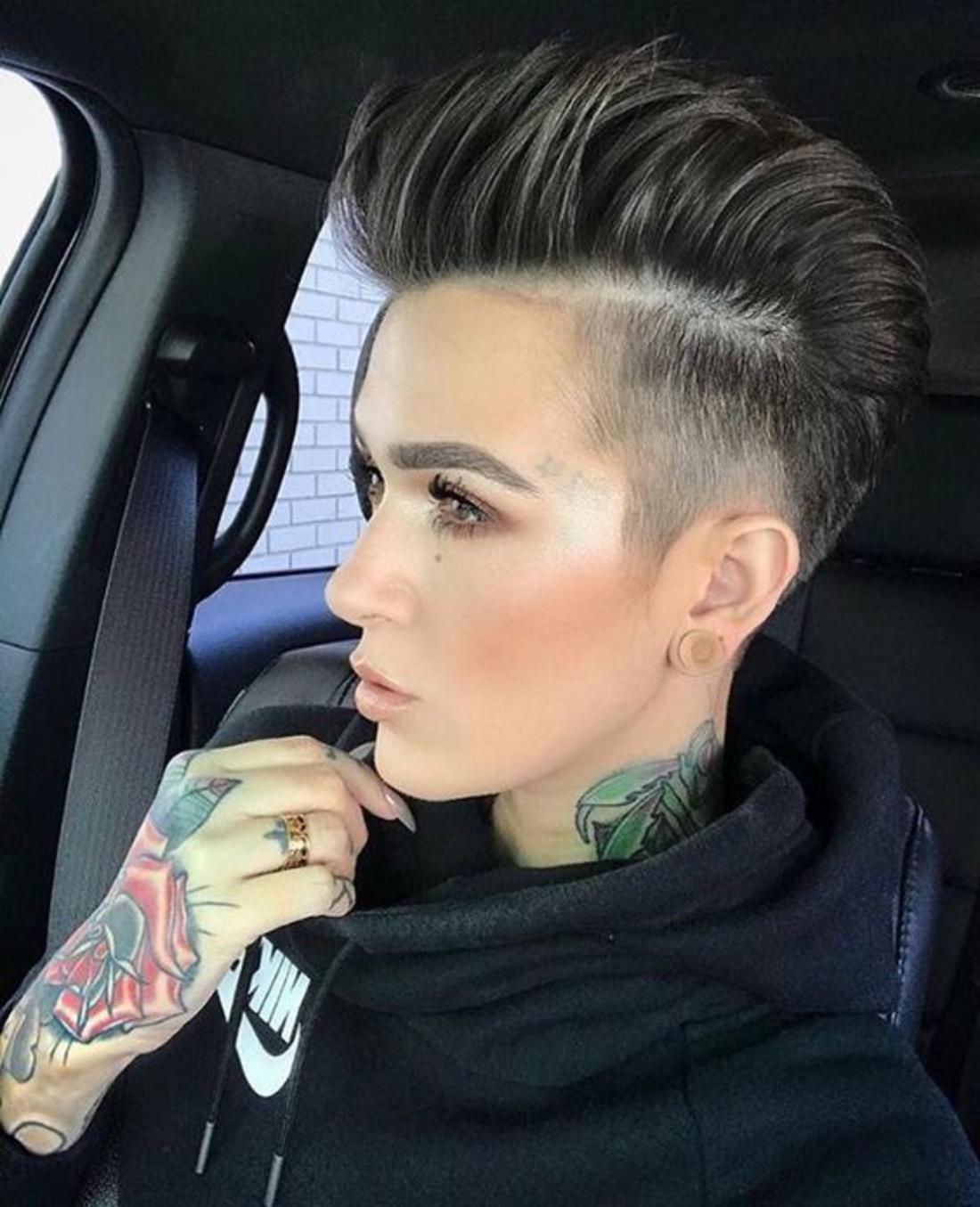 Undercut hinten Frau schwarze Haare aus einer Subkultur mit vielen bunten Tattoos