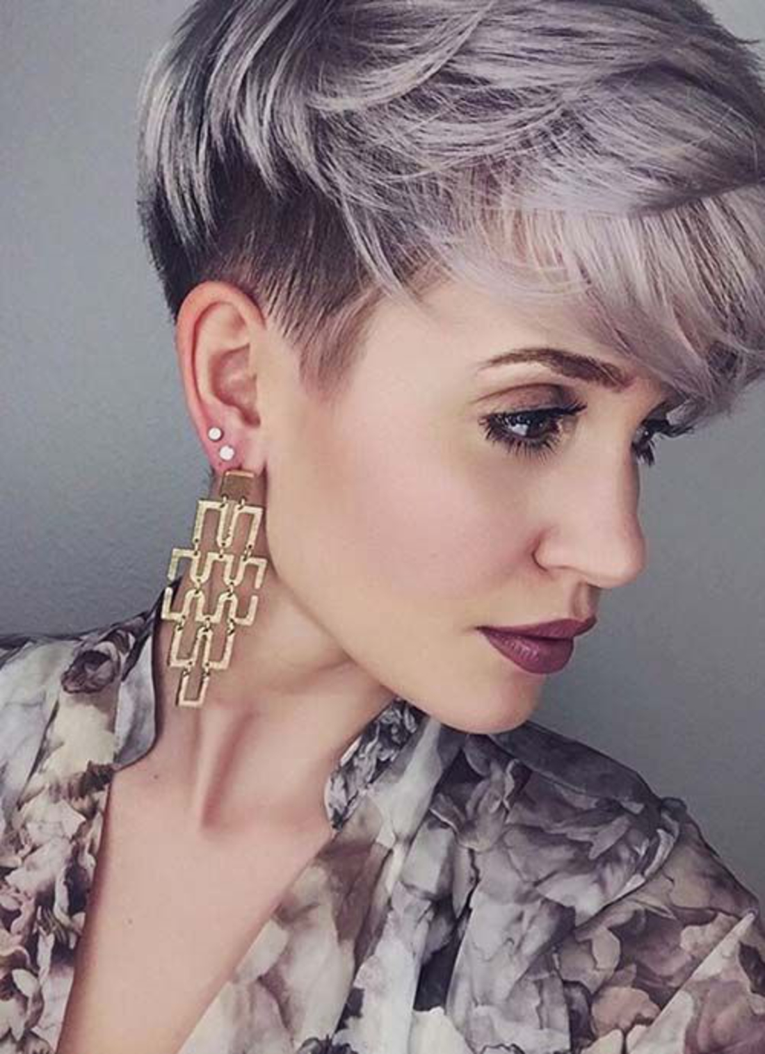lila und schwarzes Kurzhaar Undercut schöne geometrische Ohrringe, roter Lippenstift