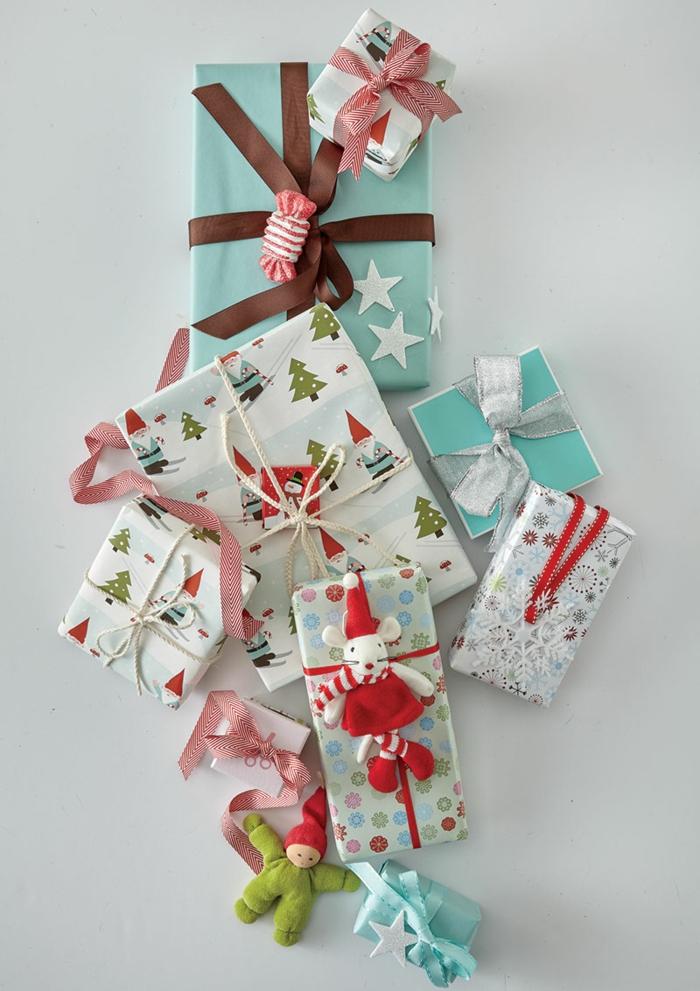 ein paar Geschenke mit kleinen Puppen dekoriert zu Weihnachten - Geschenke verpacken Anleitung
