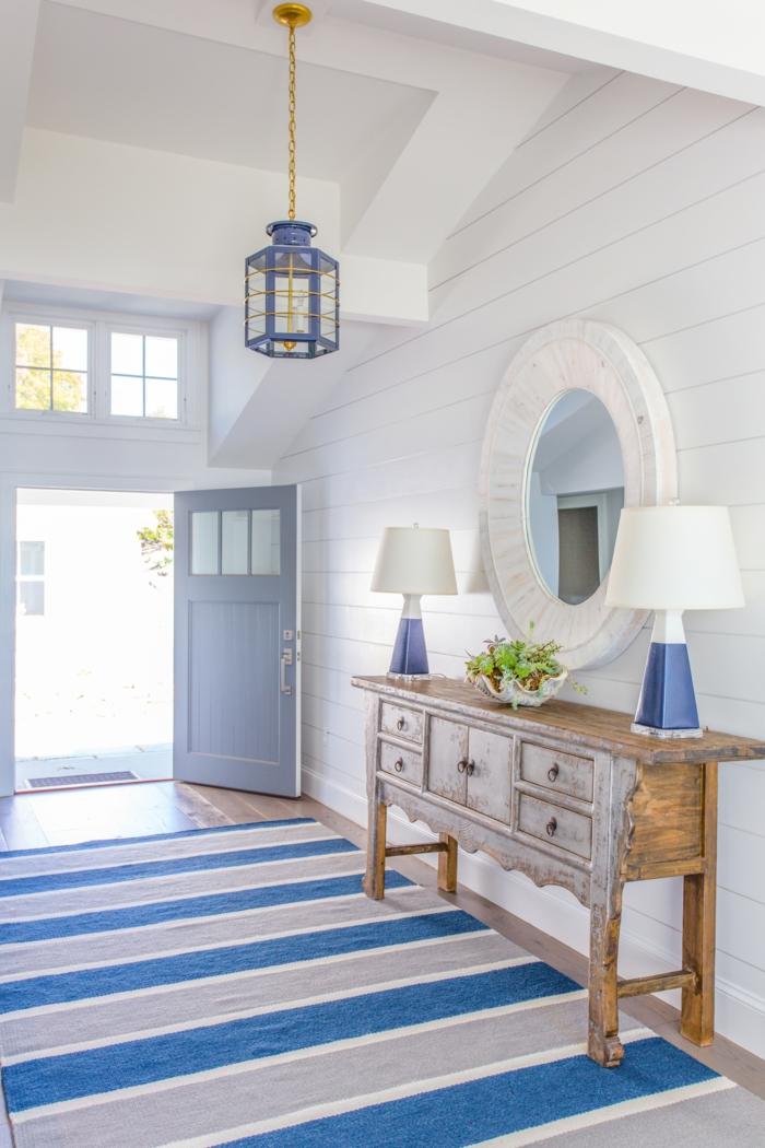 Teppich maritim in blau und grau, Kommode aus Holz mit zwei blauen Lampen, großer runder Spiegel, blaue Tür