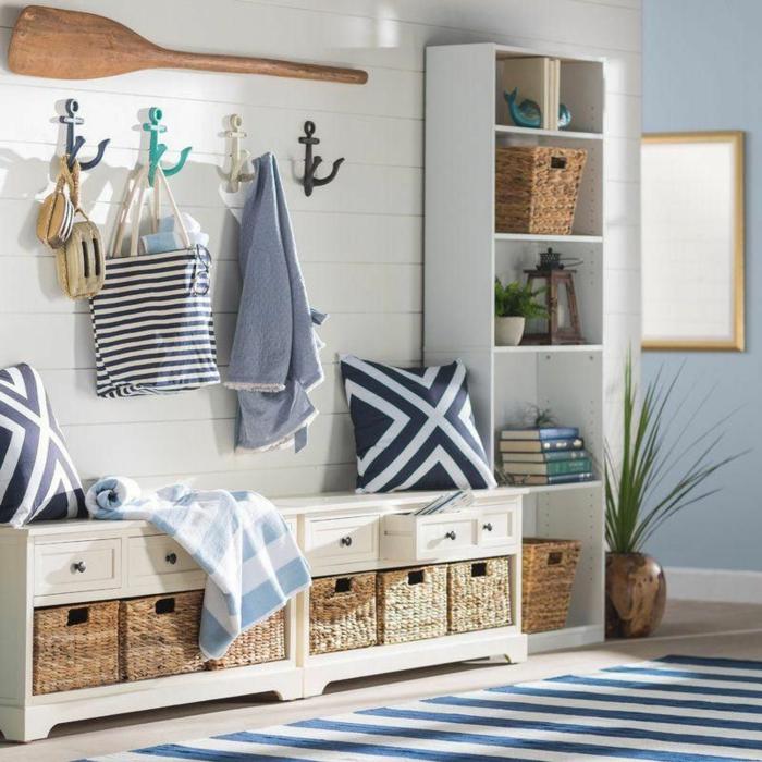 Vorzimmer Maritime Einrichtung, weiße Wand mit aufgehängte Ruder aus Holz, zwei Kissen in blauen Tönen, maritimer teppich in blau und weiß