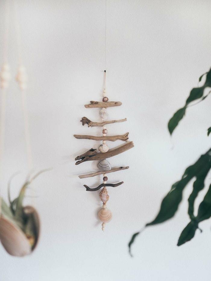Dekoration im maritimen Stil, Treibholz Deko hängend mit vielen Muscheln auf einem Faden, grüne Pflanzen im Hintergrund