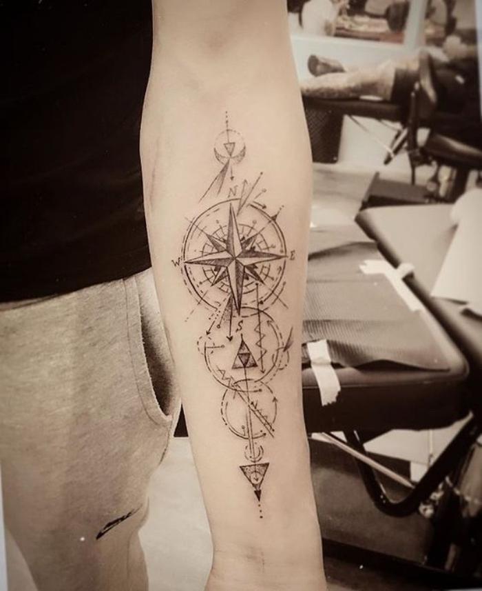 das ist eine idee für einen compass tattoo mit einem schwarzen kompass mit langen großen schwarzen pfeilen