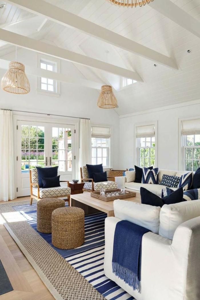 geräumiges Wohnzimmer mit großen weißen Sesseln, maritime Farben, dunkelblaue Kissen und Decken, Teppich in blau und weiß,