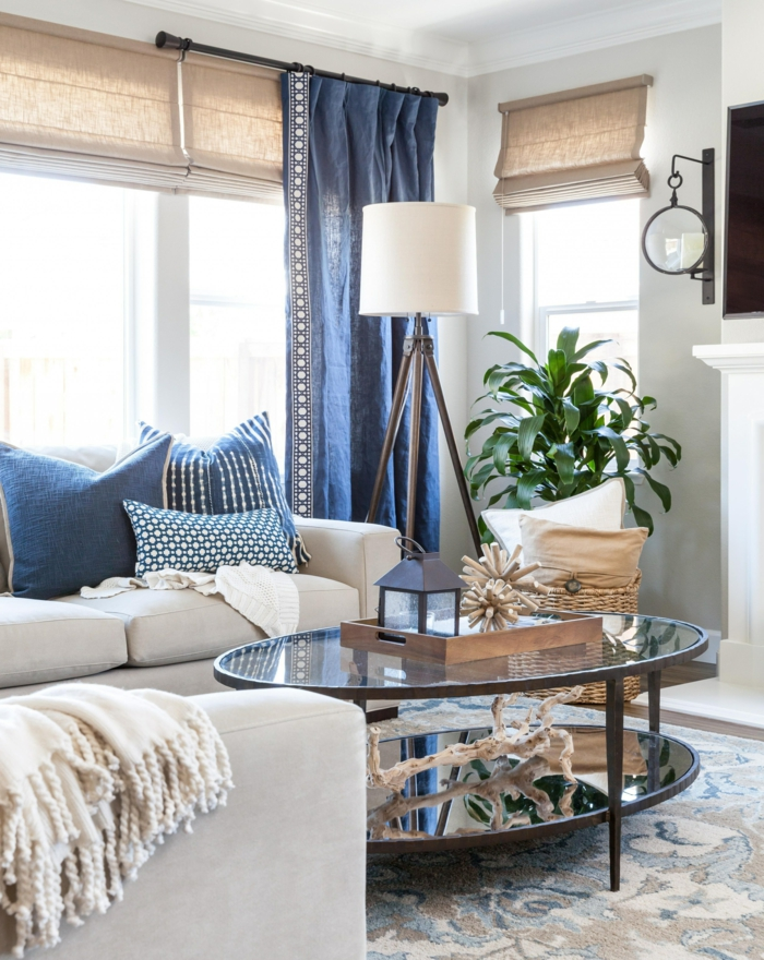 Wohnzimmer maritimer Stil, blaue Gardinen und Kissen, Sofa in beige, grüne Pflanze, runder Glastisch, Teppich mit blauen Motiven