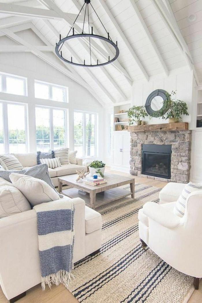 großes Wohnzimmer im maritimen Stil, zwei große Sofas in weiß, blaue Kissen, maritime Einrichtung, Decke in blau und weiß