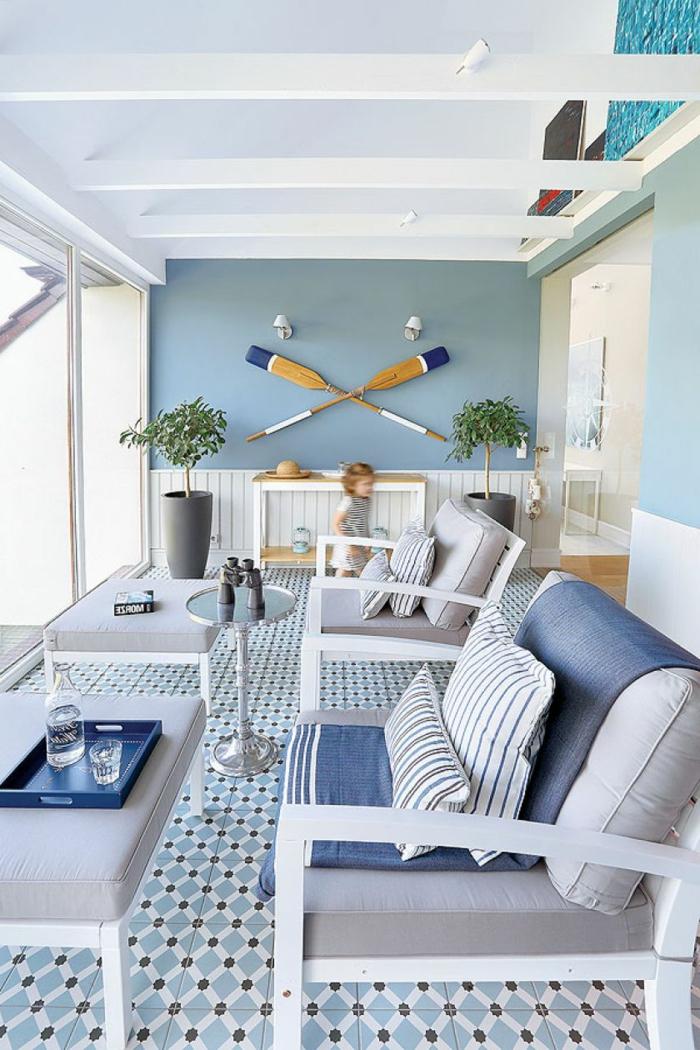 Wohnzimmer maritimer Stil, zwei große graue Sessel mit blauer Decke, zwei aufgehängte Ruder an blaue Wand,