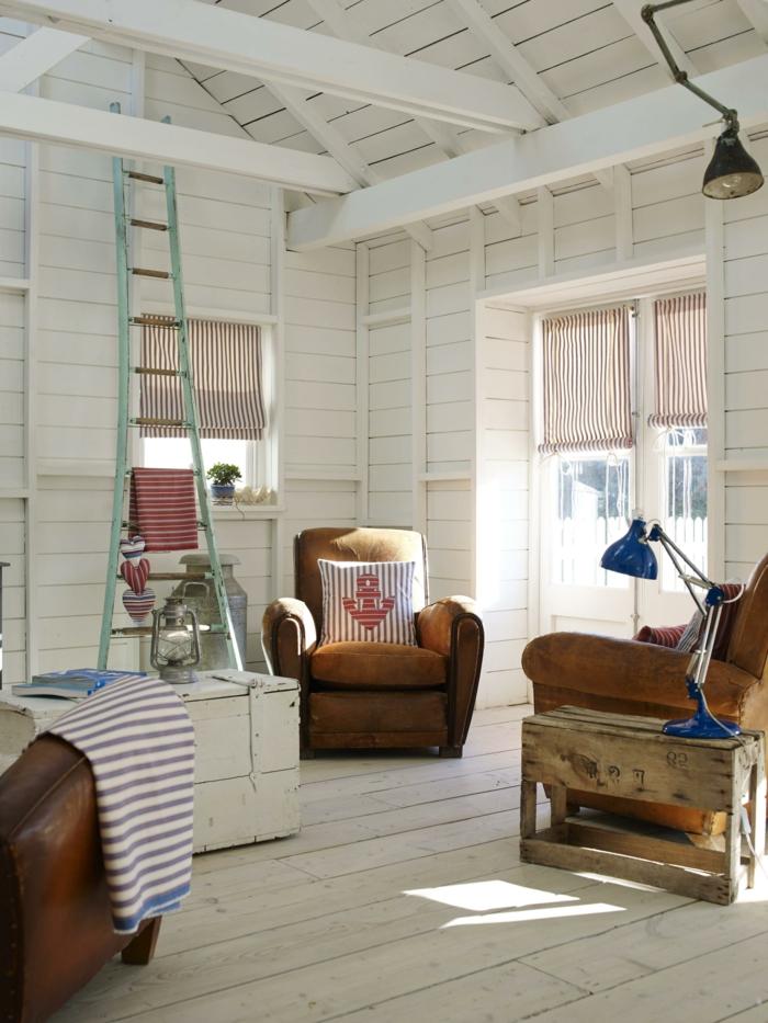 Wohnzimmer maritimer Stil mit Dachschrägen, drei Sessel aus Leder, weiß blaue Kissen mit Anker Bild, blaue Lampe,