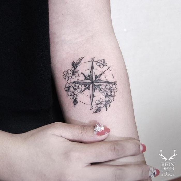ein schwarzer kompass mit kleinen weißen blumen - idee -für einen compass tattoo