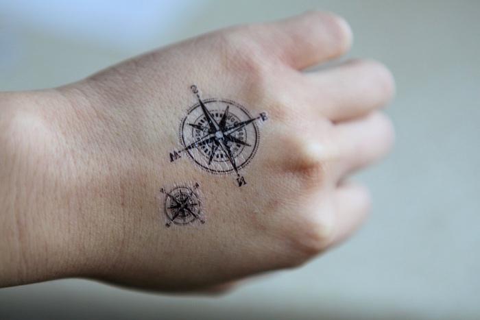 zwei schöne kleine compass tattoos mit schwarzen kompassen auf der hand
