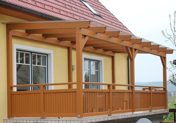 Terrassenüberdachung Holz braun Lasuren Balkon Idee gelbe Fassade
