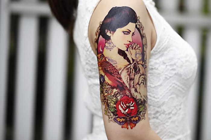tattoos für frauen, frau mit weißer bluse mit spitze und bunter tätowierung am oberarm