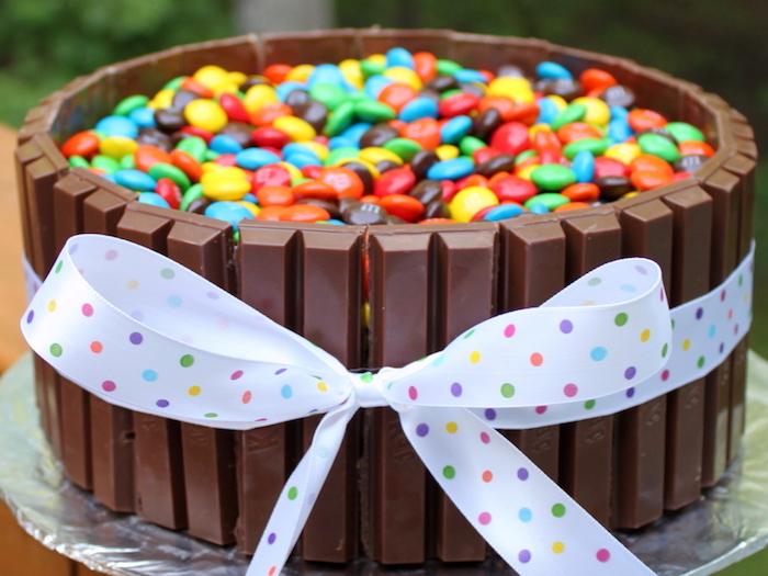 geburtstagskuchen backen, torte mit kitkat dekoriert mit bunten bonbons und schleife