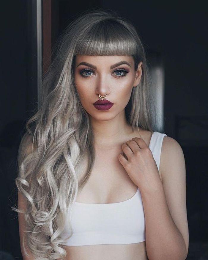 dame mit weißem top und langen grau-blonden haaren, ponyfrisur