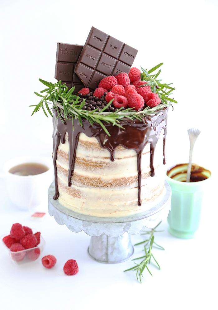 geburtstagskuchen backen, torte mit vanille dekoriert mit himbeeren, schokolade und rosmarin