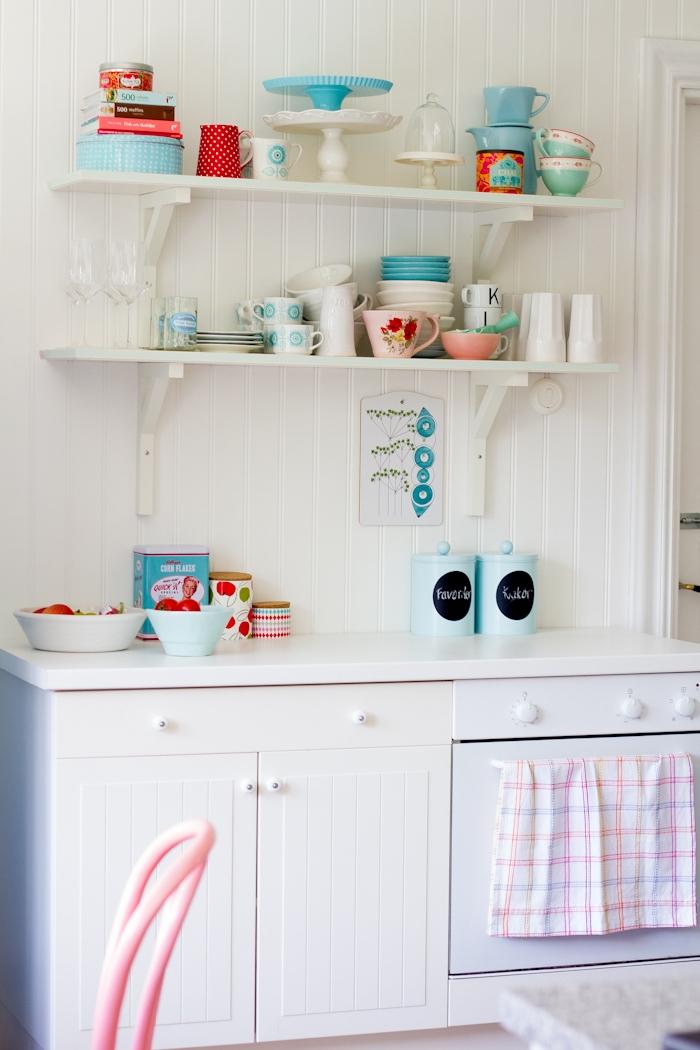 küche im shabby chic-stil, weiße schränke, hölzerne regale mit tassen und tellern