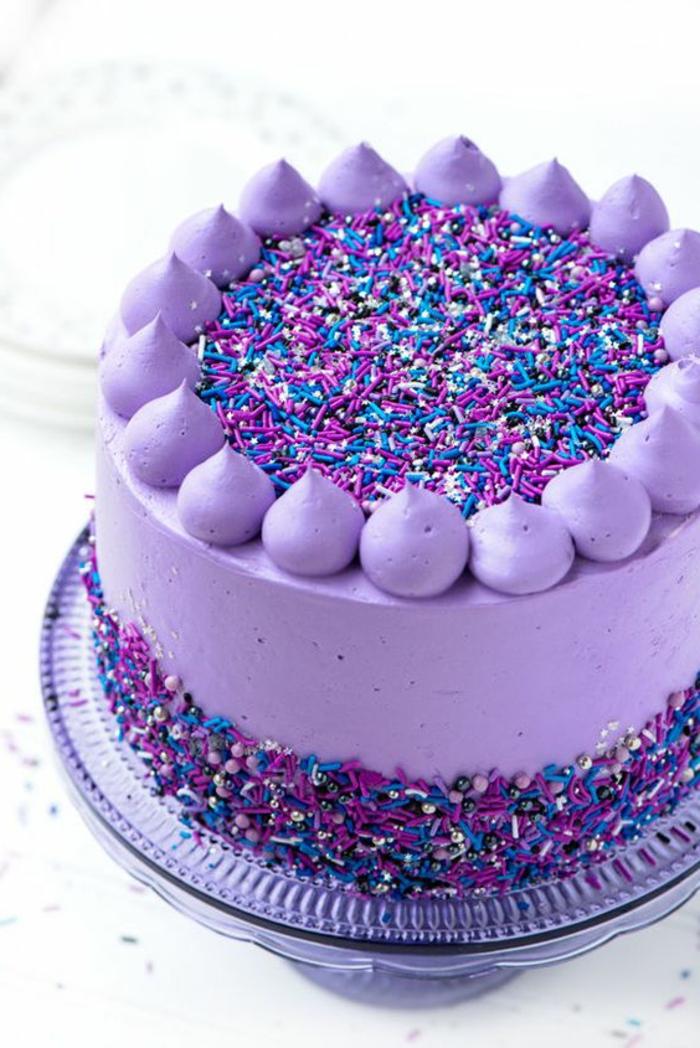 Torte lila dekoriert mit raspeln zucker creme sahne teller glas