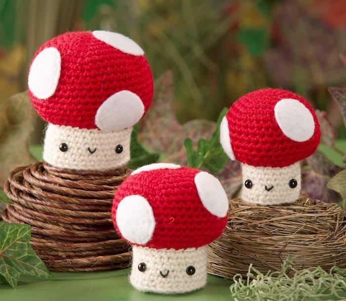 Amigurumi Anleitung drei Pilze schön arrangiert mit rotem Käppchen und schwarzen Munden und Augen