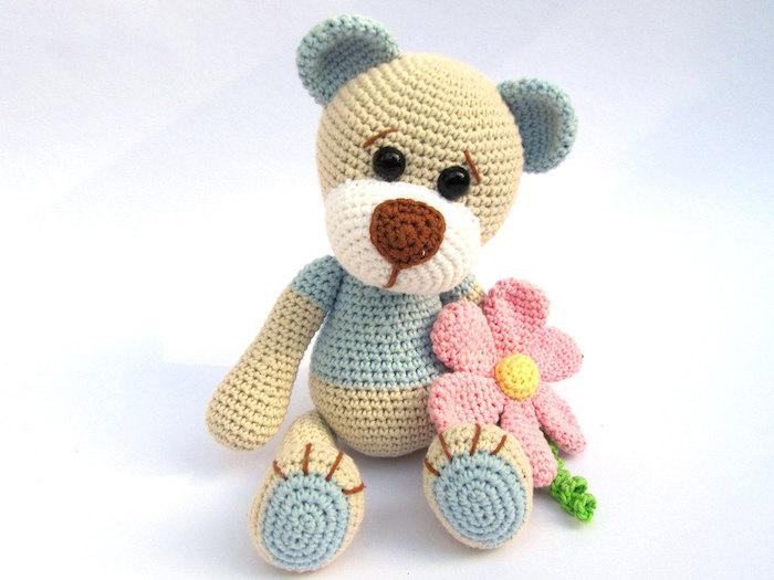 ein entzückender Teddy in einigen Farben, der Bär hat rosa Blume in der Hand - Amigurumi für Anfänger