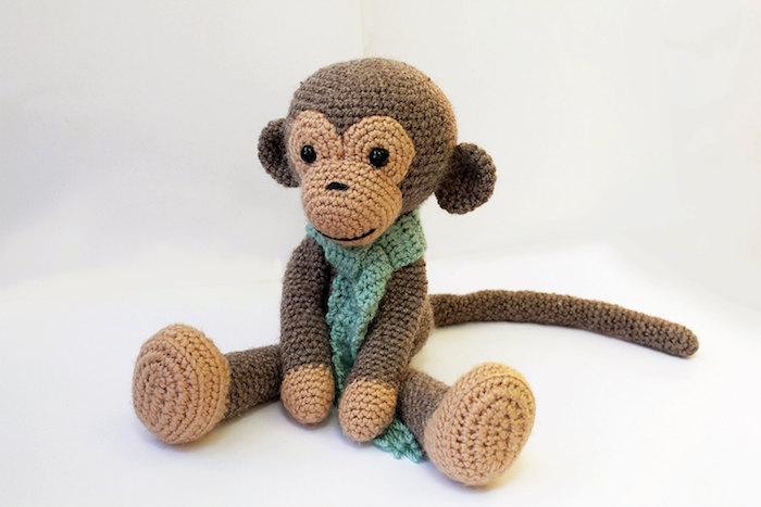 ein niedlicher Affe in brauner Farbe mit einem grünen Schal - Amigurumi Häkelanleitung