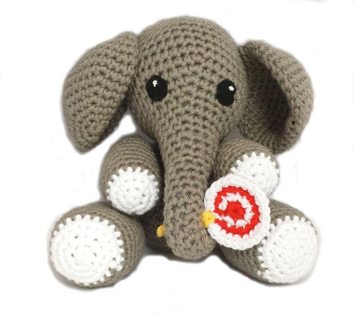 ein Elefant in grauer Farbe mit einem großen Lutscher in dem Rüssel
