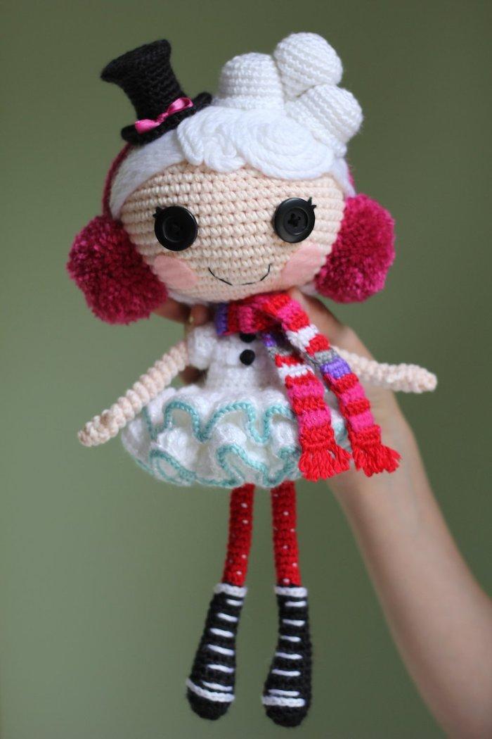 eine niedliche Puppe in einem weißen Kleid und buntem Schal - Amigurumi Häkelanleitung