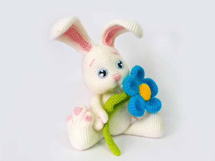 zu Ostern häkeln, ein Osterhase in weißer Farbe mit einer blauen Blume