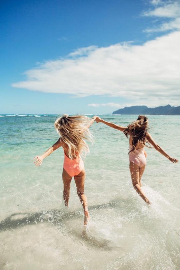 exklusive bademode zwei freundinnen gehen ins wasser baden und schwimmen meer spaß haben
