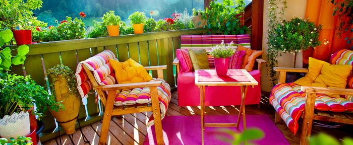 gemütliche und frische Atmosphäre auf dem Balkon, Möbel in grellen Farben und viele Blumentöpfe