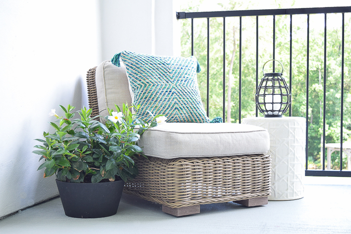Balkoneinrichtung- Rattansessel, kleiner Tisch, Balkonpflanze und Kerzenhalter