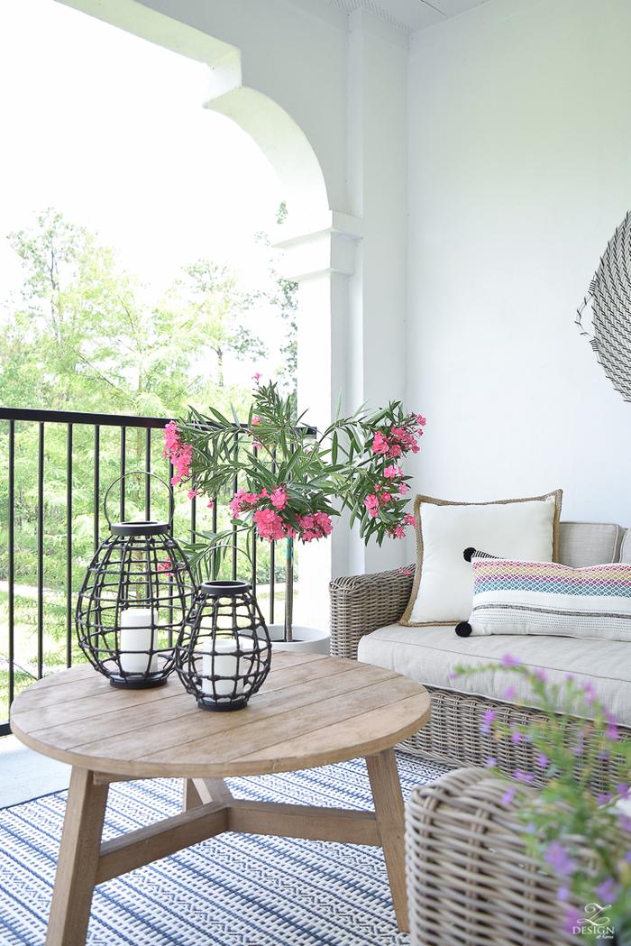 Balkoneinrichtung- Holztisch und Rattansofa, rosa Oleander, Ideen für Balkonbepflanzung