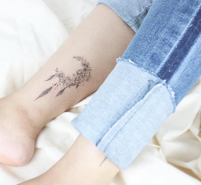 Dreamcatcher Tattoo an der Wade, Halbmond aus Blumen mit drei Federn