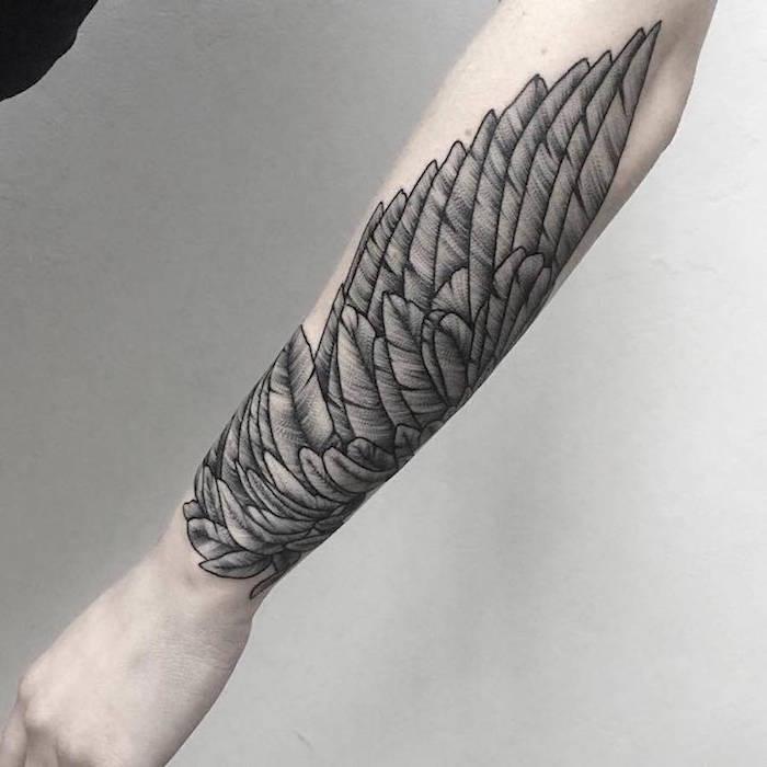 Tattoo realistic ein Flügel in schwarzer Farbe am ganzen Arm Kontrast mit der blassen Haut