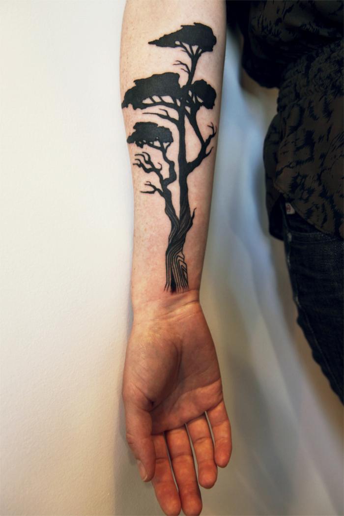 ein hoher Baum mit breiten Stamm, ein Schattenriss Tattoo realistic am Arm